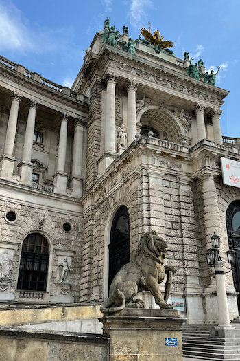 The Austrian National Library in Vienna photographed from the outside. A large lion statue is placed at the entrance.