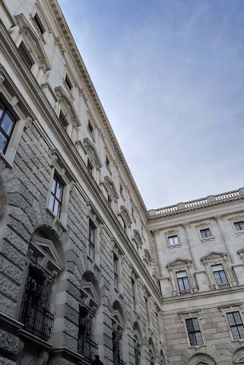 You can the see one of the buildings from the Hofburg in Vienna. The photo is shot from below and you can see the blue sky. The building has a lot of windows and a lavish facade.