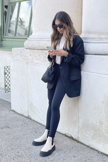 Sonia Dhillon wearing CPH735 vitello nature. She is leaning against a wall of the Hofburg in Vienna and looking at her mobile phone.
