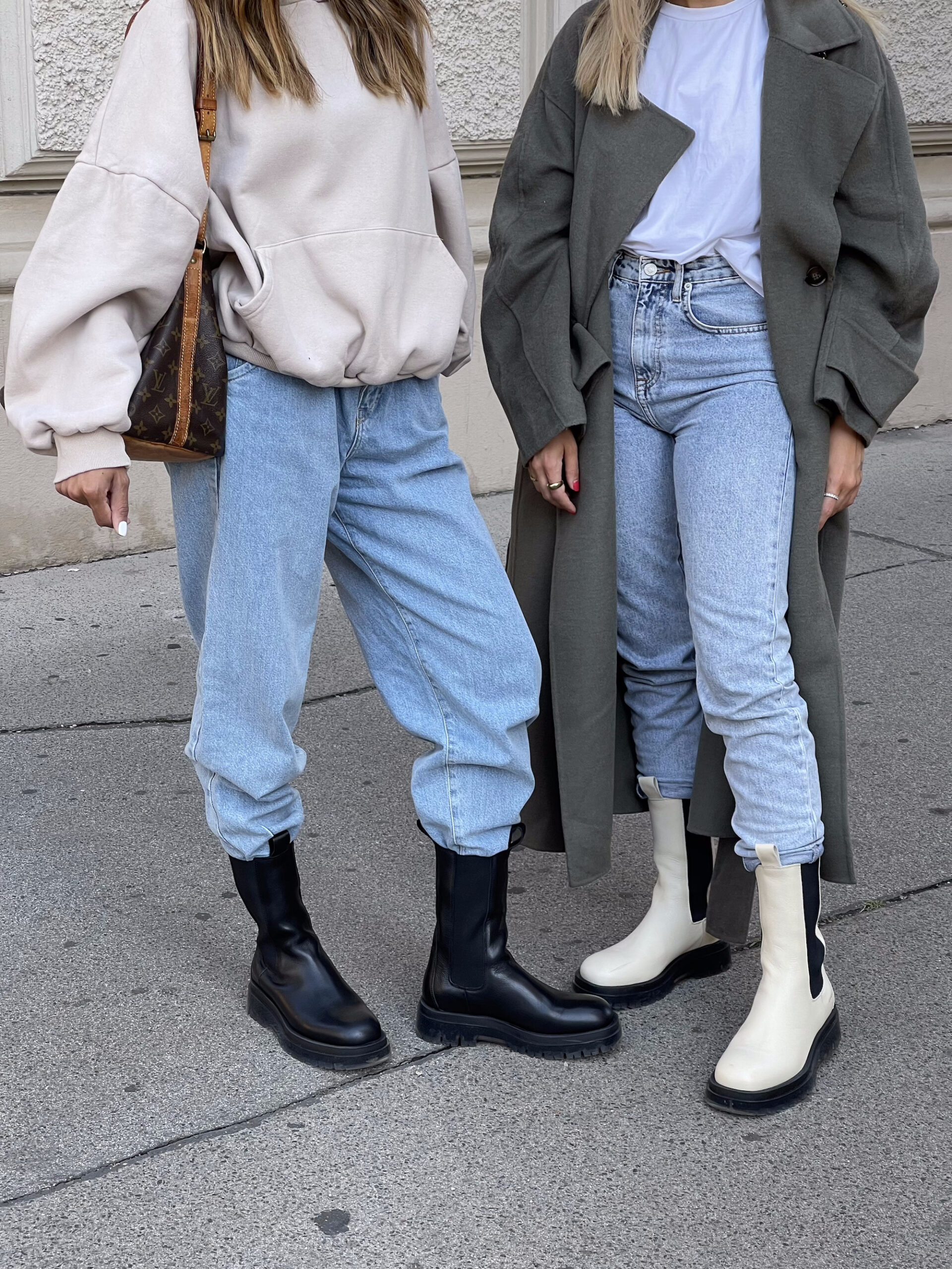 Lower body of the two influencers Sonia Dhillon and Christina Biluca. Christina Biluca is on the right, wearing denim mom jeans, a white t-shirt, a khaki trench coat and the CPH1000 in vitello ecru. To her left is Sonia Dhillon wearing light denim mom jeans, a cropped hoodie in beige, the CPH1000 in clear black and carrying a Louis Vuitton around her right shoulder.