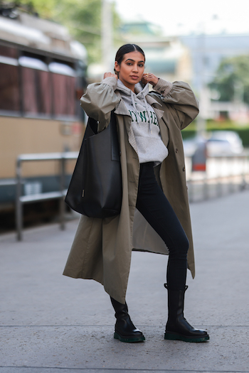 Sonia Dhillon wearing a khaki trenchcoat, a black denim jeans, a grey hoodie with green print on it, a copenhagen Bag 1 in vitello black and the CPH1000 in vitello black/green. She is standing on the streets of Vienna. Behind her you can see a train.