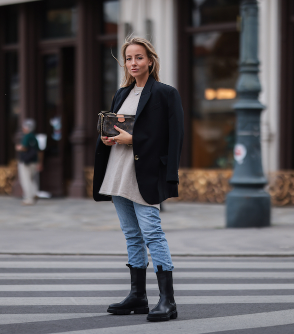 Influencer Christina Biluca on the streets of vienna, wearing CPH500 in vitello black combined with a light blue jeans, a beige pullover and a black blazer. In her hand she is holding a small louis vuitton bag.