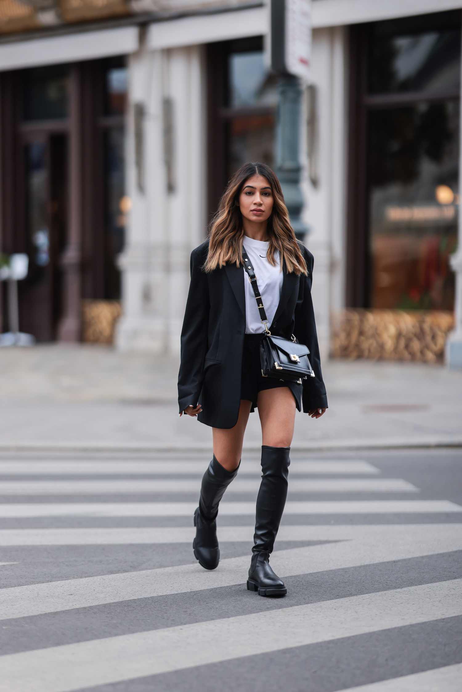 Sonia Dhillon walking across a zebra crossing in Vienna. She is wearing CPH544 Overknee Boots in vitello black, a black shorts, a white T-shirt from Nike, a oversized blazer in black and a crossbody bag.
