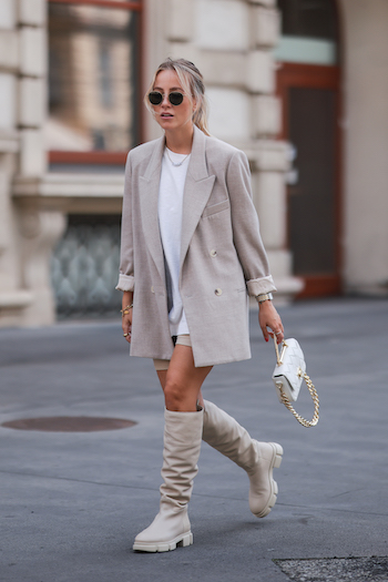 Christina Biluca walking of the streets of Vienna with her CPH551 in vitello nature. She combined the boots with a beige shorts, a long and white Tshirt, a beige Blazer and cool sunglasses. In her hand she holds a white bag.