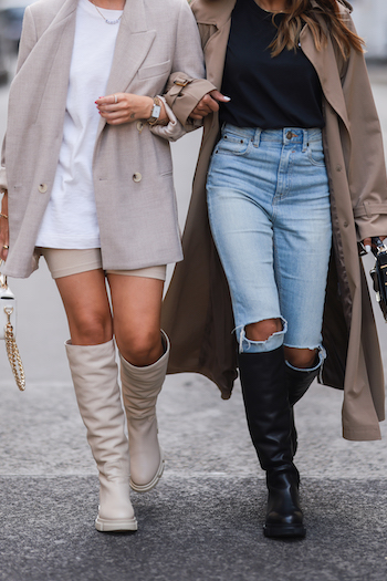Christina Biluca and Sonia Dhillon walking along the streets of Vienna. You can see a section of her outfits. Christina is wearing CPH551 in vitello nature, a beige shorts, a long and white Tshirt, and a beige Blazer. Sonia Dhillon is wearing a beige trenchcoat, light blue destroyed denim jeans, a black Tshirt and CPH551 in vitello black.