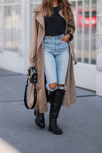Sonia Dhillon is wearing a beige trenchcoat, light blue destroyed denim jeans, a black Tshirt and CPH551 in vitello black. In her hand she holds a black bag.