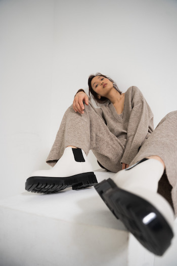 Picture from the Lookbook shooting of the Autumn Winter Collection 2021 from Copenhagen Studios. Model is sitting on a white block and stretch out one leg. She is wearing a beige cashmere set. The outfit is combined with the CPH1001 Boot in Vitello Eggshell.
