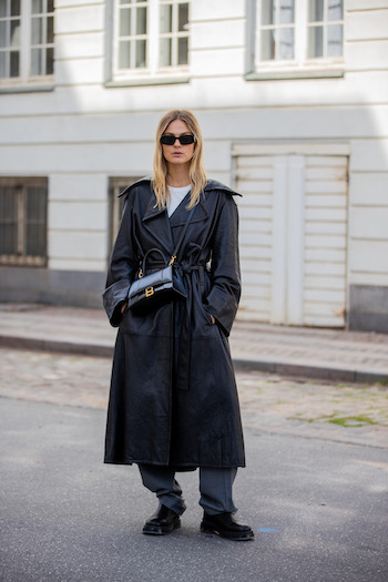 @alessawinter wearing a black leather coat, wide and long grey fabric trousers. She combined our CPH1001 vitello black clear to this outfit. With her cool black sunglasses on, she stands on the streets of Copenhagen.