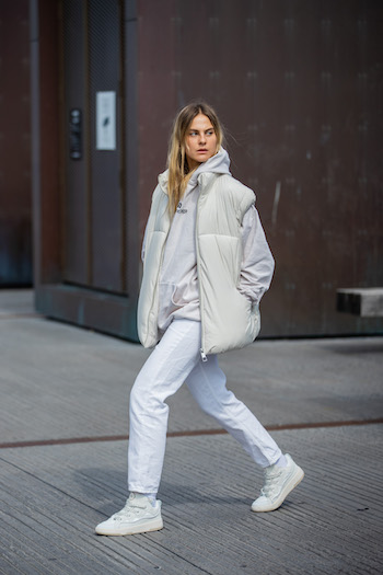 You can see @alessawinter running on the streets of Copenhagen in her all white look. She is wearing a white puffer vest, white jeans, and a white hoodie in combination with the CPH201 leather mix white.