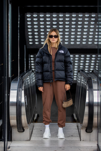 @alexawinter is standing in front of the escalator. She wears a dark brown loungewear suit in combination with a black puffer jacket from The North Face, the CPH40 in vitello white and cool black sunglasses.