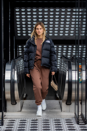 @alexawinter is standing in front of the escalator and comes running towards the photographer. She wears a dark brown loungewear suit in combination with a black puffer jacket from The North Face and the CPH40 in vitello white.