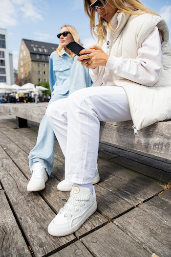 @alessawinter and @mariehindkaer sitting on a bench in Copenhagen. @mariehindkaer wearing her all denim look with CPH461 calf white and @alessawinter her all white look in combination with CPH201 Leather mix white. While sitting @alessawinter writes a text message on her mobile phone.