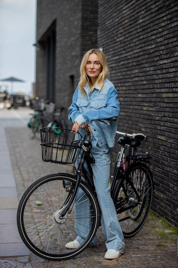 @Mariehindkaer on the Copenhagen Streets with her bike. She wears a light blue denim Look from head to toe and a pair of CPH461 calf white.