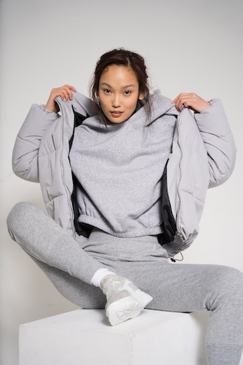 Campaign Picture from the Lookbook Shooting Autumn Winter 2021 from the brand Copenhagen Studios. Model is sitting on a white block and is wearing a grey monochrome outfit with CPH51 Material Mix Sneakers. The Outfit consists of a grey leggings, a grey hoodie and a grey puffer jacket.