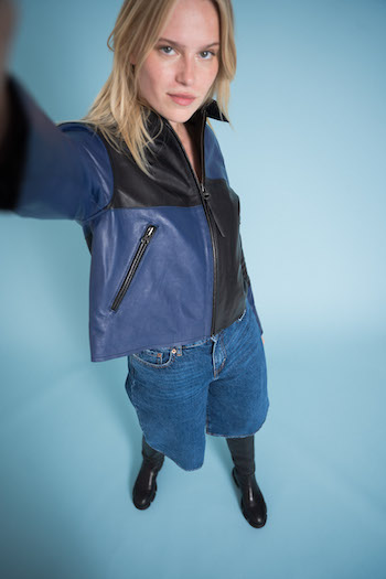 Campaign picture from the tone in tone shooting from Copenhagen Studios. Model is standing and pretending to do a selfie with the camera. She is wearing knee length pants a black and blue leather jacket and the CPH551 Vitello black knee boots.