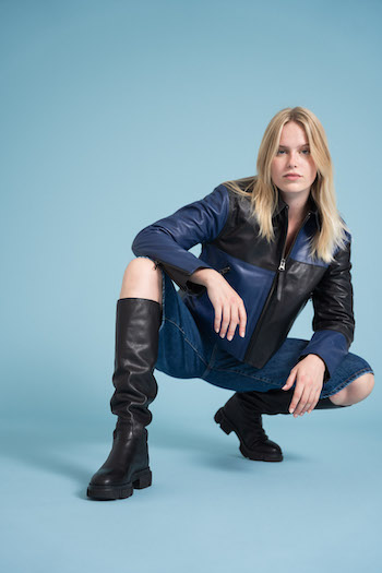 Campaign picture from the tone in tone shooting from Copenhagen Studios. Model is sitting in a squat position and looking into the camera. She is wearing knee length pants a black and blue leather jacket and the CPH551 Vitello black knee boots.