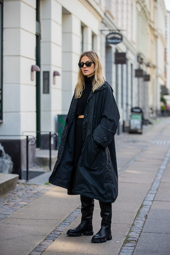 You can see @alessawinter standing on streets of Copenhagen in her all black everything look. She is wearing a black oversized raincoat from Balenciaga, a black turtleneck sweater, a black skirt, black sunglasses and the CPH551 in vitello black.
