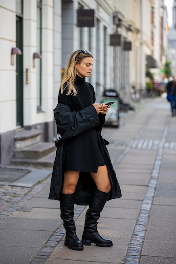You can see @alessawinter standing on streets of Copenhagen in her all black everything look. She is wearing a black oversized raincoat from Balenciaga, a black turtleneck sweater, a black skirt and the CPH551 in vitello black. With her black sunglasses on her head, she is reading a message on her mobile phone.