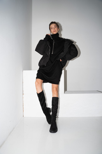 Picture from our Lookbook Shooting Autumn Winter 2021. The model leans against a white lock. She is wearing a black oversized sweater dress with a black puffer jacket and the Copenhagen cph556 costa black kneeboots.