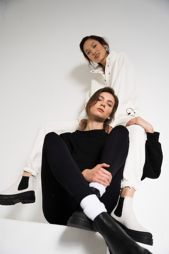 Lookbook Picture from the Autumn Winter Collection 2021 of Copenhagen Studios. Two models are sitting. One is sitting higher on a block. Picture is made from a low perspective. One model is wearing a white jogger set with the CPH1001 Eggshell and the other model is wearing a black sweater and black leggings with the CPH1001 in Vitello black with white tennis socks.